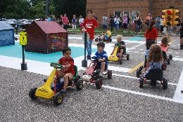 children in pedal cars navigate through Safety Town with the supervision of a youth volunteer