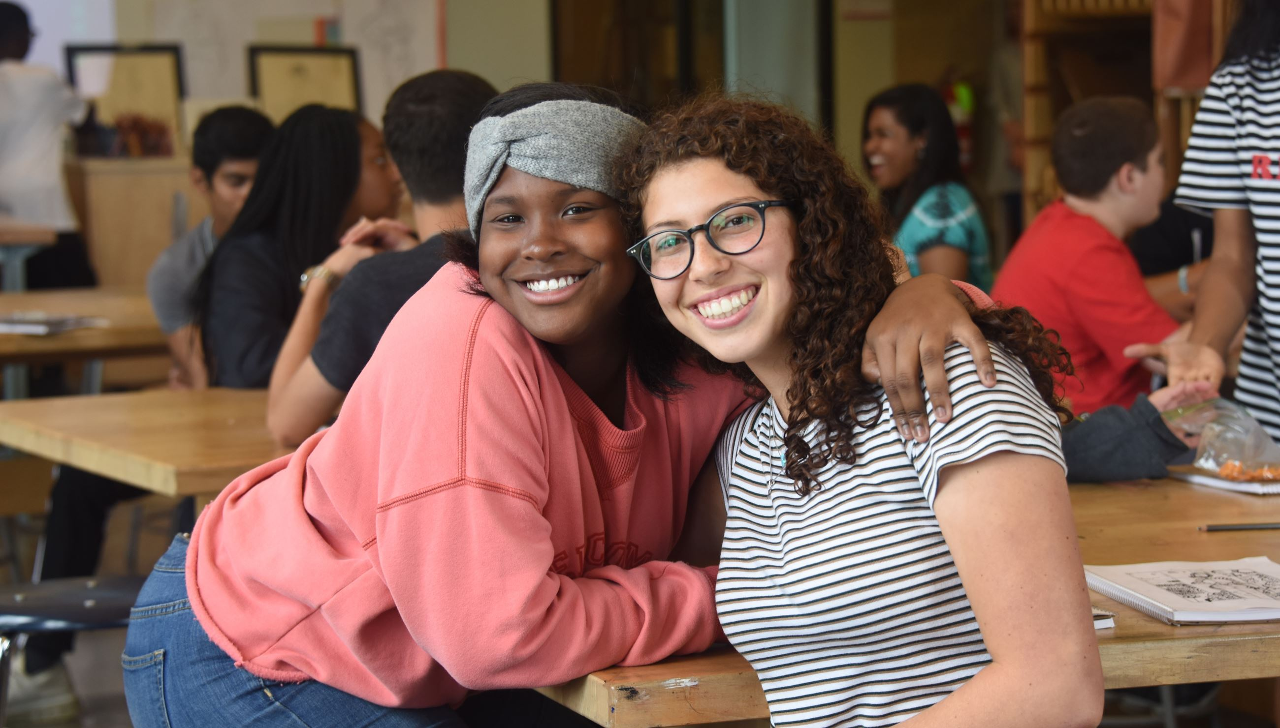 Two young women with their arms around each other smile at the camera
