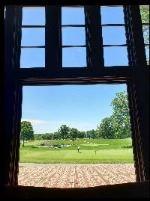 Exterior view through a window of a man putting a golf ball