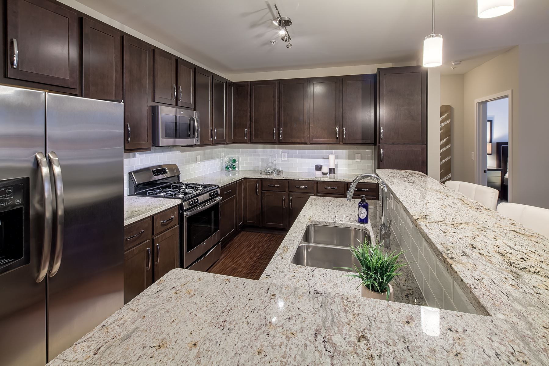 Beautifully appointed kitchen with a gas stove, gooseneck faucet, and stainless-steel appliances