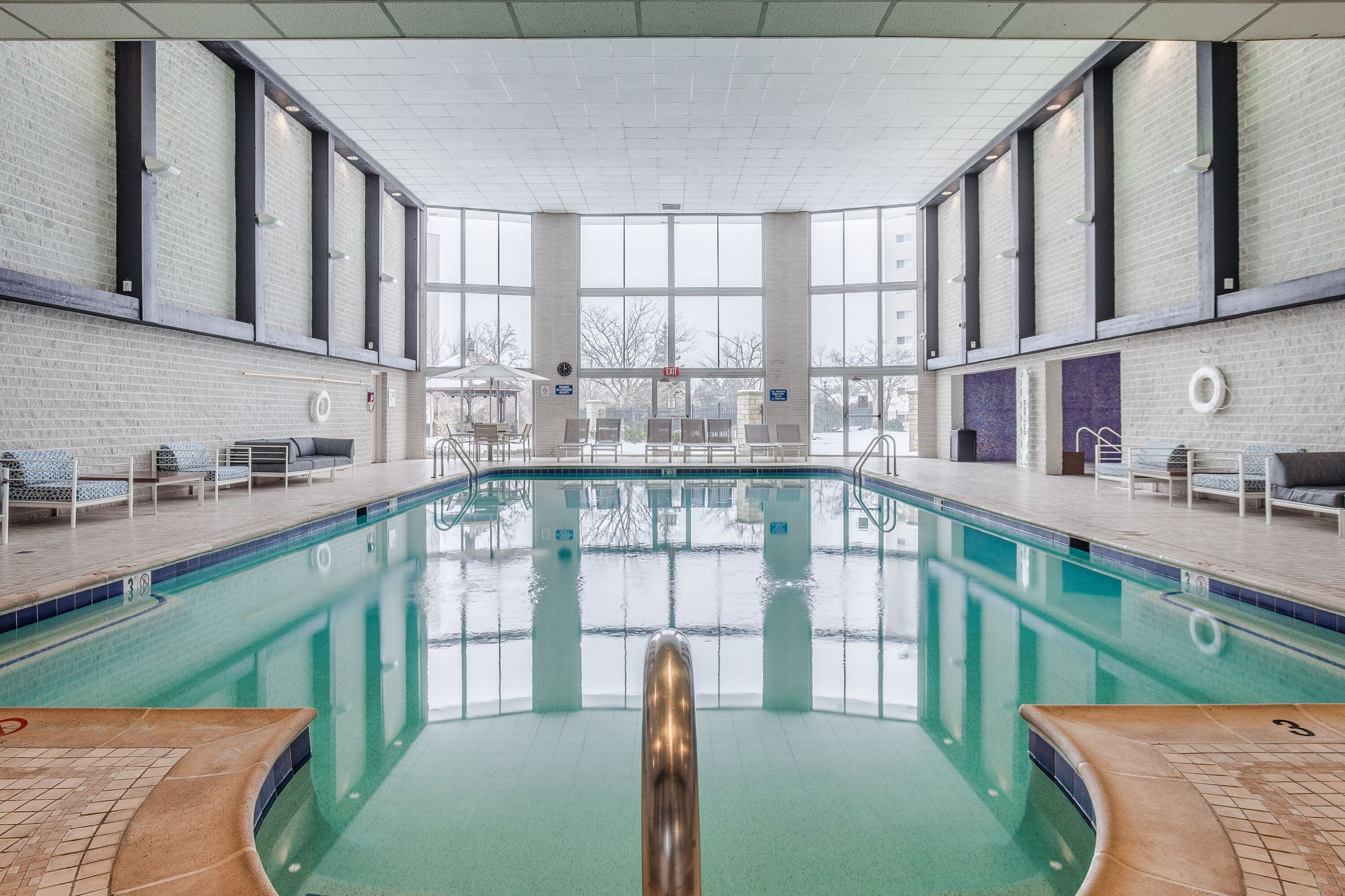 View of an indoor swimming pool and a wall of windows at the far end